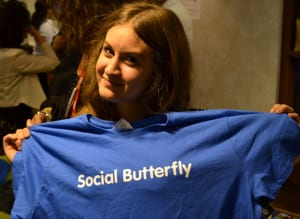 woman holding up social butterfly t-shirt