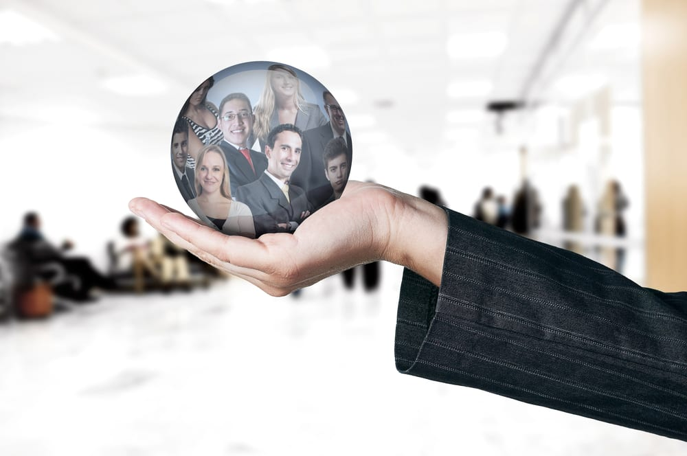 Hand holding a globe with reflection of business people