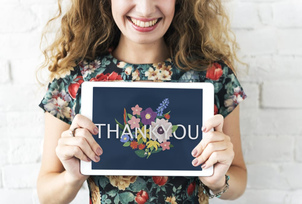 happy woman holding a thank you sign