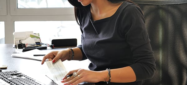 woman cutting payroll checks at her desk