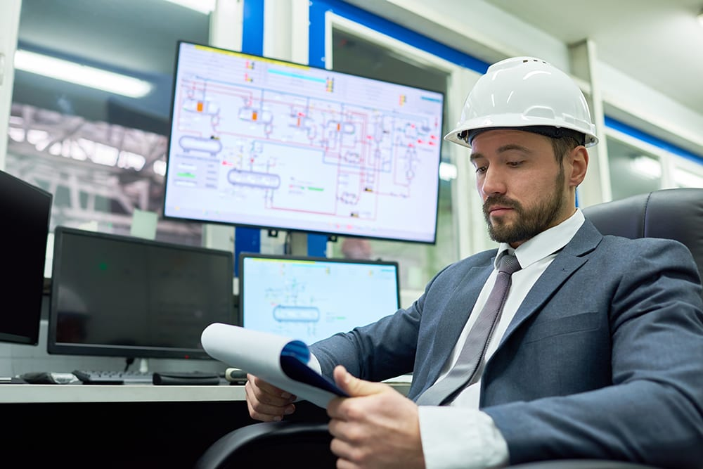 man wearing white hard hat reviewing reports on clipboard