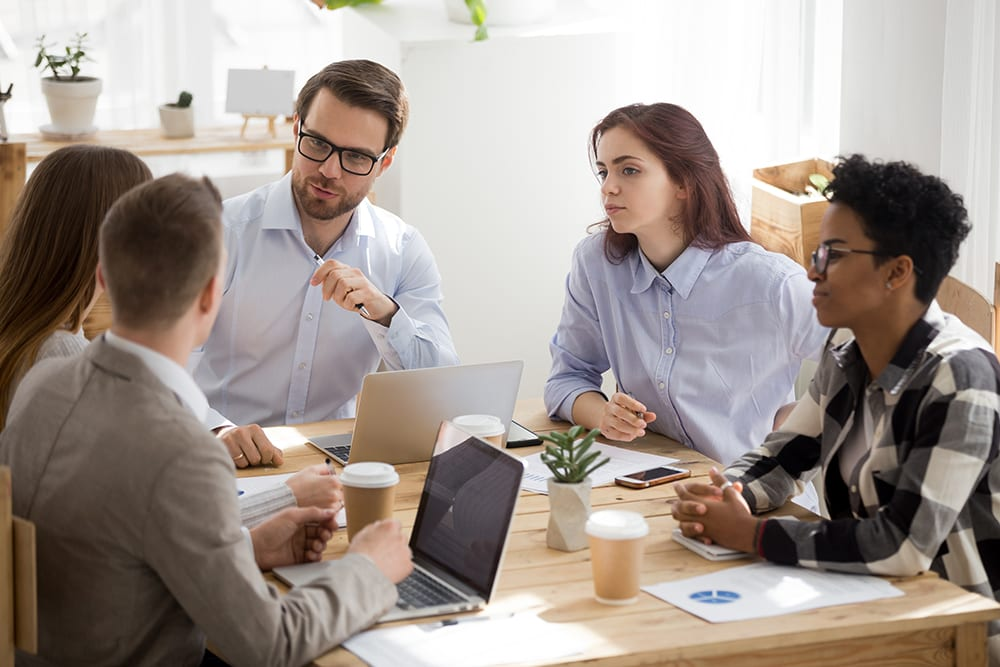 small group of employees siting around table discussing a small business hr consulting firm