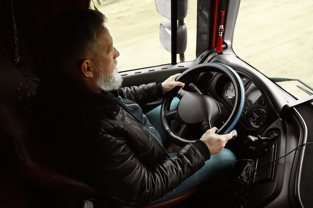 truck driver sitting in cab of truck