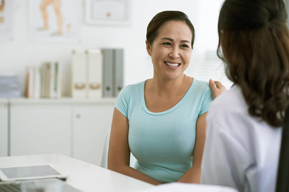 Doctor physician consulting with patients in hospital exam room