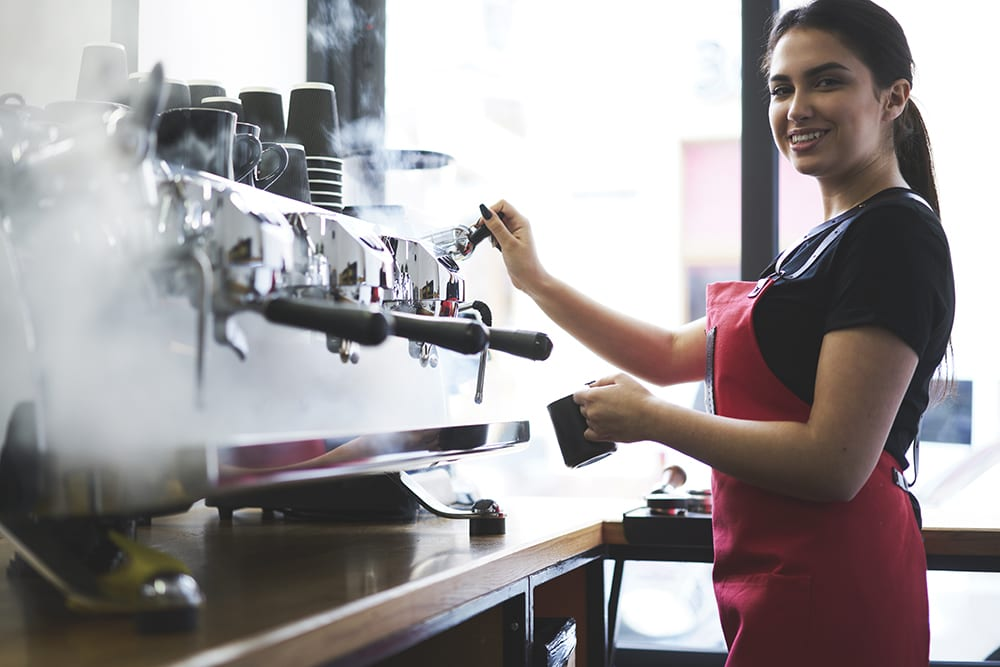 employee working at coffee machine for franchise business
