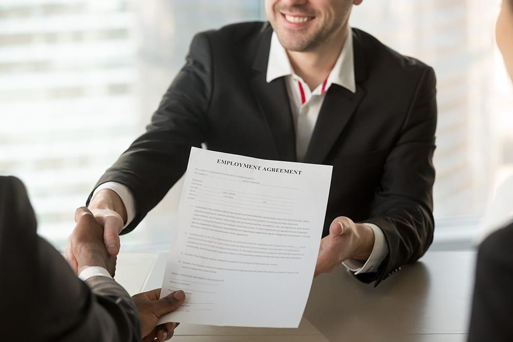 employer handing employee agreement to new hire